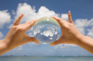 Saipan. One hands is holding a glass sphere and it projects the sky and the clouds at the beach.